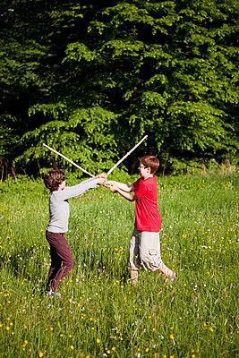 Jungen beim Stockkampf im Park - p1195m1138136 von Kathrin Brunnhofer