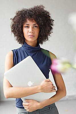Hübsche Geschäftsfrau mit Afro steht in einem Büro und hält ihren Laptop in der Hand  - p1301m2020155 von Delia Baum