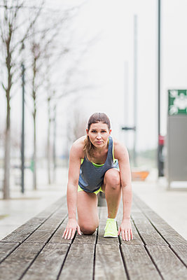 Woman in starting position on wooden bench - p300m1204587 by Anke Scheibe