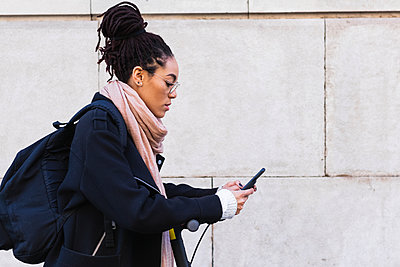 Jamaican woman with dreadlocks using smart phone while leaning on push scooter by wall - p300m2243979 by NOVELLIMAGE