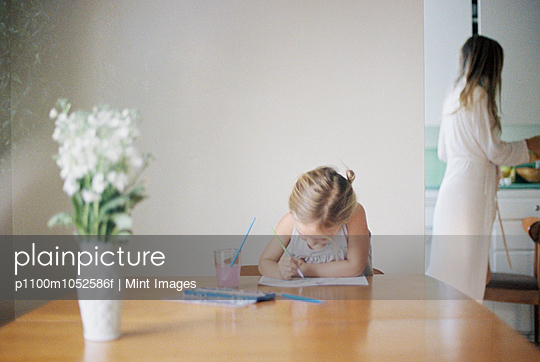 Young girl sitting at  a table, painting, a vase with white flowers, a woman in the background. - p1100m1052586f by Mint Images