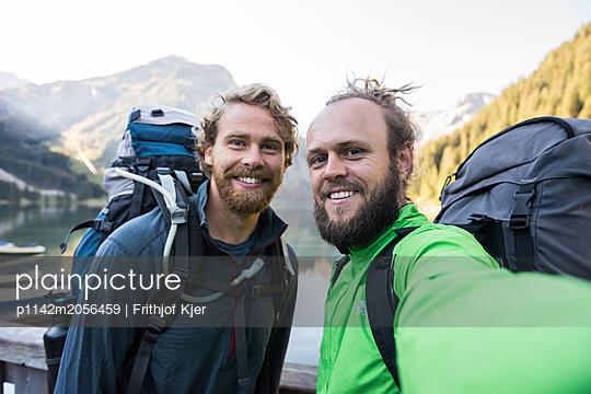 Zwei Wanderer machen Selfie an Bergsee - p1142m2056459 von Runar Lind