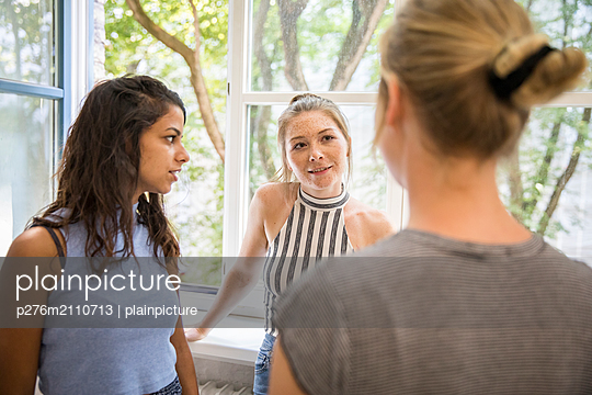 Young women in a conversation  - p276m2110713 by plainpicture