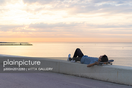 Young Chinese man with skateboard lying on wall at the beach - p300m2012283 von VITTA GALLERY