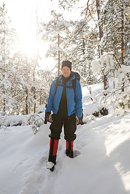Man hiking in sunny forest in winter - p1687m2278475 by Katja Kircher