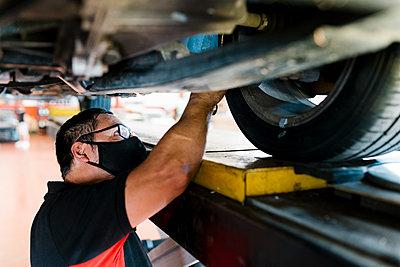 Close-up of male mechanic wearing mask examining tire in garage - p300m2220817 by Ezequiel Giménez