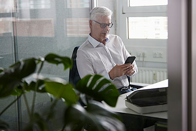 Mature businessman using mobile phone while sitting in office - p300m2282761 by Rainer Berg