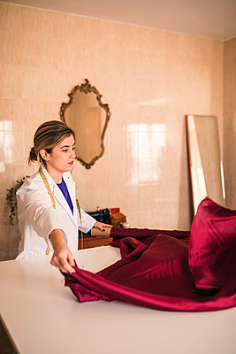 Female fashion expert holding maroon fabric while working at workshop - p300m2293508 by LUPE RODRIGUEZ