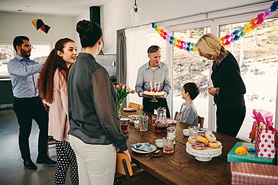 Grandfather showing birthday cake to boy while happy family enjoying at party - p426m1580225 by Maskot