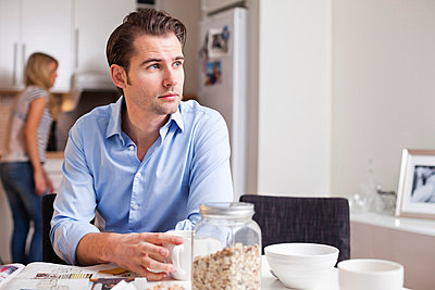 Mid adult man looking away while having coffee at table with woman in background - p426m803237f by Maskot