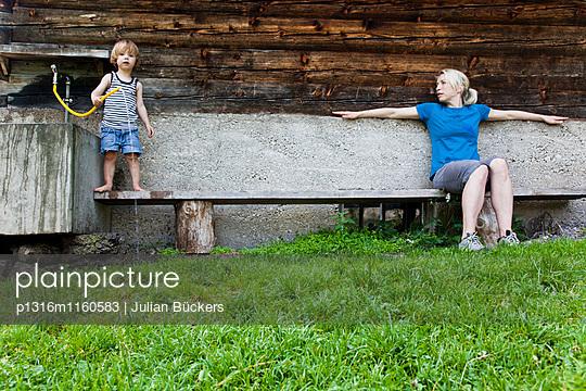 Frau und Kind auf einer Bank vor einem Bauernhaus, Kloaschauer Tal, Bayrischzell, Bayern, Deutschland - p1316m1160583 von Julian Bückers