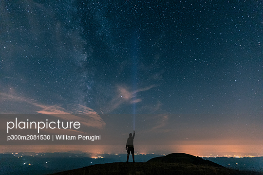 Italy, Monte Nerone, silhouette of a man with torch under night sky with stars and milky way - p300m2081530 by William Perugini