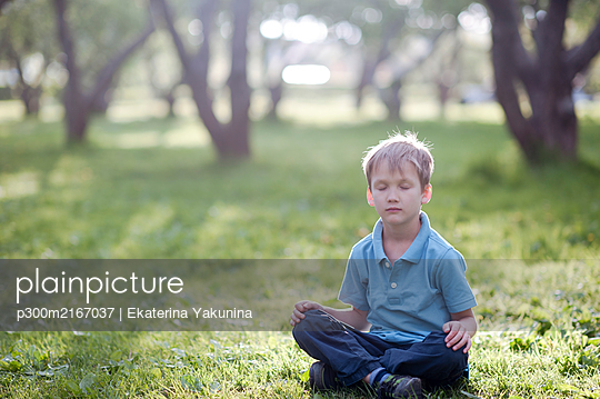 Portrait of little boy sitting with closed eyes on a meadow - p300m2167037 by Ekaterina Yakunina