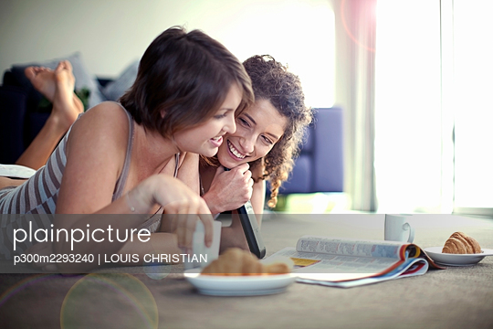 Smiling woman looking at female friend reading magazine while lying in living room - p300m2293240 by LOUIS CHRISTIAN