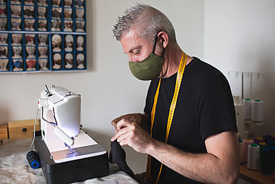 a mask-wearing tailor at work with his sewing machine - p1166m2279603 by Cavan Images