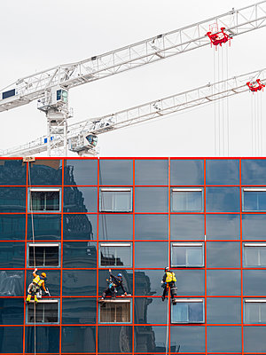Great Britain, Birmingham, Industrial window cleaners hanging and construction cranes in the background - p1280m2244972 by Dave Wall