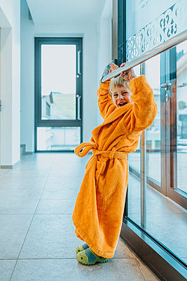 Cheerful boy in bathrobe leaning on railing at hotel - p300m2266788 by Mareen Fischinger