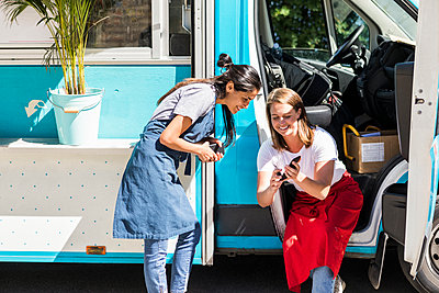 Happy young multi-ethnic female owners sharing smart phone against food truck - p426m2046467 by Maskot