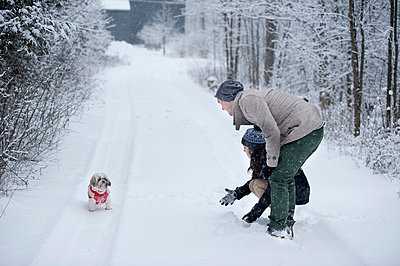 Young couple playing with dog in snow covered forest, Ontario, Canada - p429m2050876 by Sara Monika