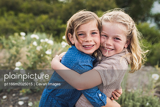 Portrait of happy sisters embracing while standing against plants in forest - p1166m2025015 by Cavan Images
