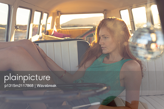 Woman relaxing on front seat of camper van at beach - p1315m2117868 by Wavebreak