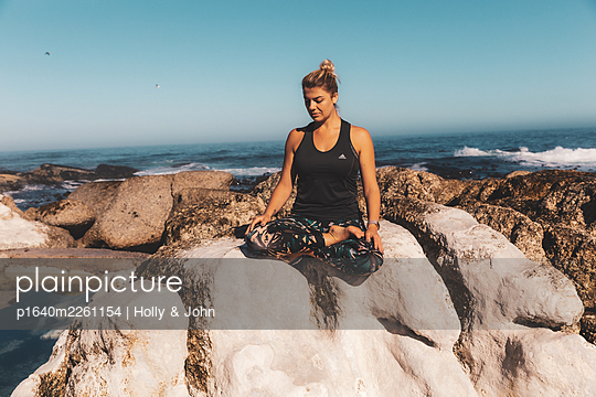 Young woman practises meditation on a rock by the sea - p1640m2261154 by Holly & John