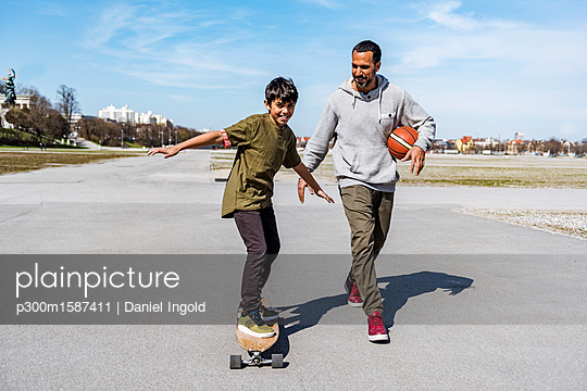 Father and son with longboard and basketball outdoors - p300m1587411 von Daniel Ingold