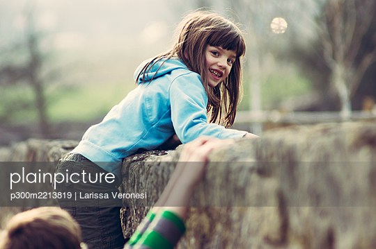 Portrait of girl climbing on wall - p300m2213819 by Larissa Veronesi