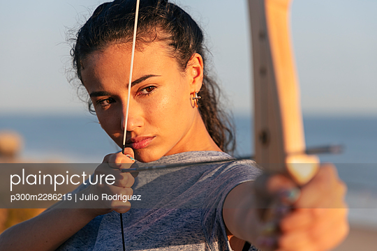 Concentrated young woman practicing archery with bow and arrow - p300m2286215 by Julio Rodriguez