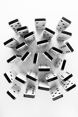 Black and white plastic dominoes standing on end and crowded together on a white surface. - p1302m2073083 by Richard Nixon