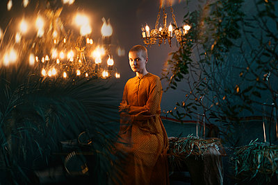 Young woman between plants in the light of ancient chandeliers - p1642m2216172 by V-fokuse