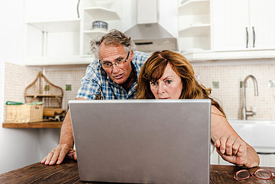 Older couple using laptop in kitchen - p429m659735f by Dan Brownsword