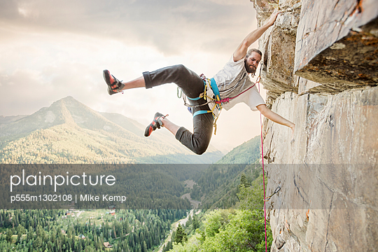 Caucasian man hanging from rock while climbing - p555m1302108 by Mike Kemp