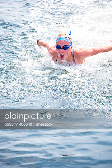Caucasian swimmer gasping for air in lake - p555m1408640 by Shestock