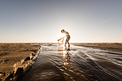 Young child walking in water with a net on a sunny morning at a beach - p1166m2108120 by Cavan Images