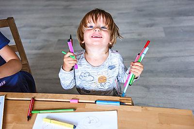 Little boy drawing with felt-tip pens - p1166m2159623 by Cavan Images