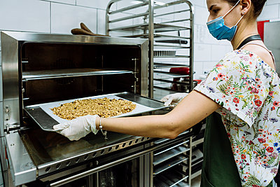 Young female baker positioning sheet in oven at bakery kitchen during pandemic - p300m2226675 by Xavier Lorenzo