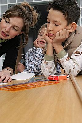 Eine Lehrerin zeichnet an einem Tisch mit zwei Schülern - Unterricht - Bildung - p4902146 von Stock4B