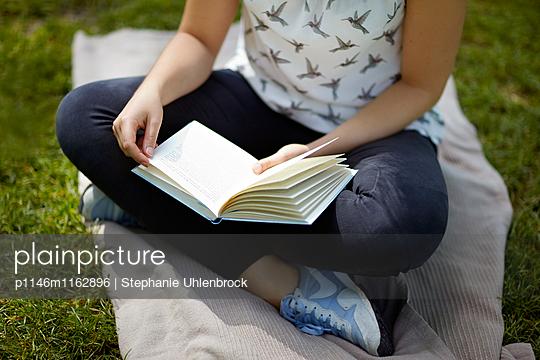 Close-Up Frau im Schneidersitz mit Buch - p1146m1162896 von Stephanie Uhlenbrock