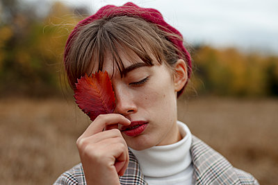Young woman with beret holding autumn leaf - p1646m2231465 by Slava Chistyakov