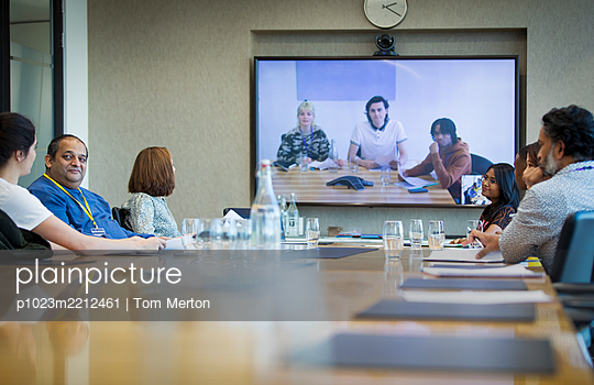 Business people video conferencing in conference room meeting - p1023m2212461 by Tom Merton