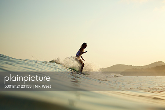Female surfer riding ocean wave - p301m2123133 by Nik West