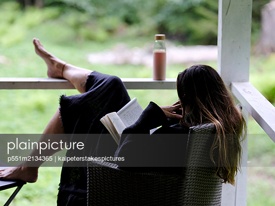 Woman reading book on the porch - p551m2134365 by Kai Peters