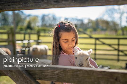 UK, North Yorkshire, Girl (6-7) holding lamb in organic farm - p924m2292509 by Monty Rakusen