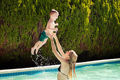 Mother playing with son in swimming pool - p1166m1096105f by Cavan Images