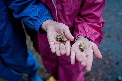 two kids standing in the rain holding two snails in their hands - p1166m2136100 by Cavan Images