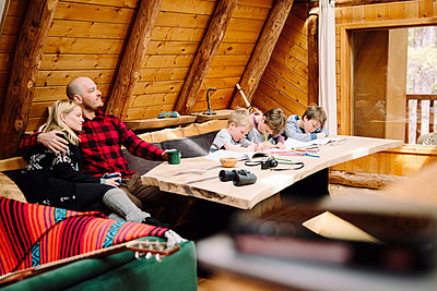 Family relaxing and coloring in cabin - p1192m2094135 by Hero Images