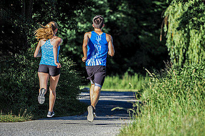 Back view of young couple jogging in park - p300m1487437 by Stefan Schurr