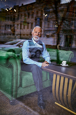 Elegant senior man sitting on couch in a cafe looking out of window - p300m1550042 by Zeljko Dangubic