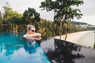Woman relaxing in infinity pool, Nai Thon Beach, Phuket, Thailand - p300m2166360 by Christophe Papke